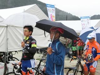 傘を差して検車を待つ(左から)窪木・岡本・山本