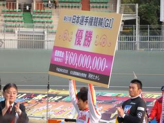 賞金ボードを掲げる村上義弘選手